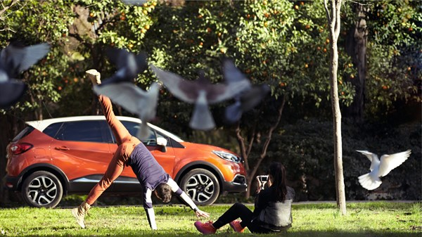 A man doing a cartwheel in front of a Renault CAPTUR